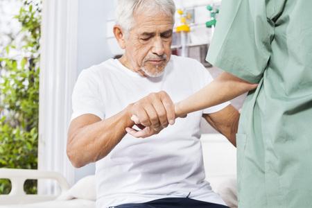 Disabled senior patient holding hand of female nurse in rehab center Archivio Fotografico