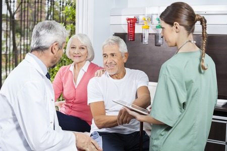 rehab: Senior couple listening to doctor while nurse holding digital tablet in rehab center Stock Photo