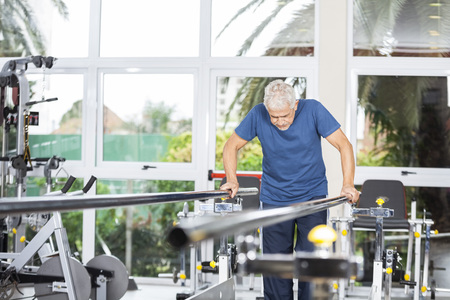 senior adults: Senior man taking support of bars while walking in fitness studio at rehab center