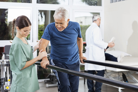 Female physiotherapist standing by senior patient walking between parallel bars in rehabilitation center Archivio Fotografico