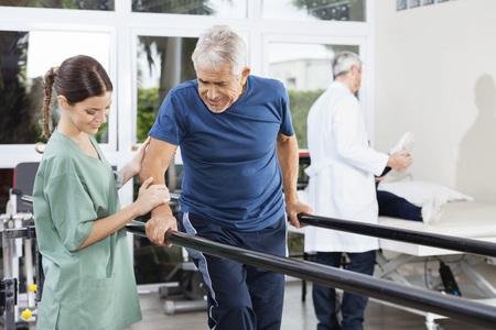 Vrouwelijke fysiotherapeut die zich door hogere patiënt lopen tussen parallelle staven in revalidatiecentrum
