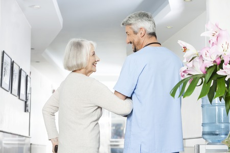 long term care services: Rear view of disabled senior woman looking at mature physiotherapist in rehab center