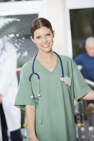 physiologist: Portrait of smiling female physiologist standing in fitness center at rehab center Stock Photo
