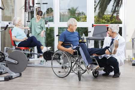 Male and female physiotherapists guiding patients to exercise at rehab fitness center