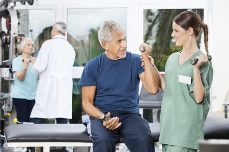 instructing: Female nurse instructing senior male patient exercising with dumbbell at rehab fitness center