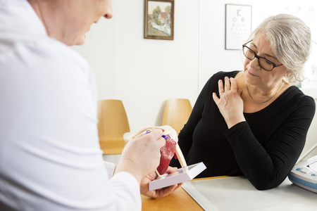 senior pain: Male doctor explaining shoulder rotator cuff model to senior woman in clinic Stock Photo