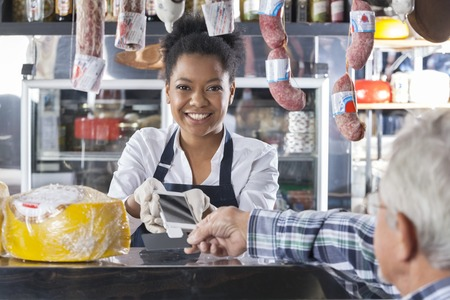 convenience store: Portrait of happy saleswoman accepting mobile payment from customer in cheese shop