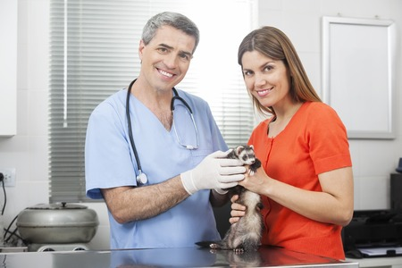 assistant: Portrait of happy mid adult woman and mature doctor with weasel in clinic