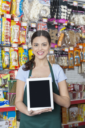 retail store: Portrait of confident saleswoman showing digital tablet with blank screen in pet store Stock Photo