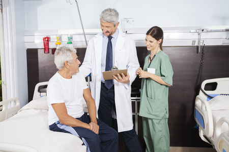 long term care services: Smiling doctor and nurse looking at senior patient sitting on bed at rehab center Stock Photo