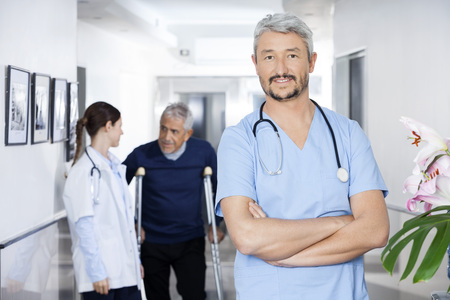 long term care services: Portrait of confident doctor standing arms crossed with colleague and senior patient in background at rehab center
