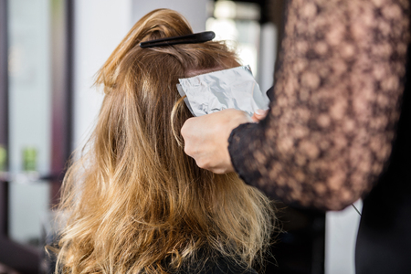 hair brush: Cropped image of beautician putting foils in female clients hair at salon