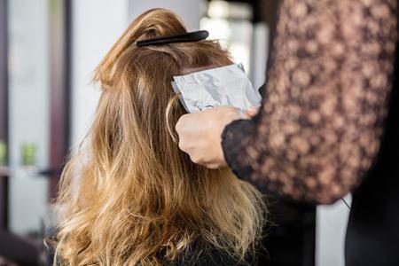 tinte cabello: Imagen recortada de esteticista poner láminas de pelo del cliente femenino en salón Foto de archivo