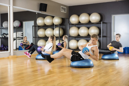 strength training: Young determined male and female friends exercising with medicine ball in gym