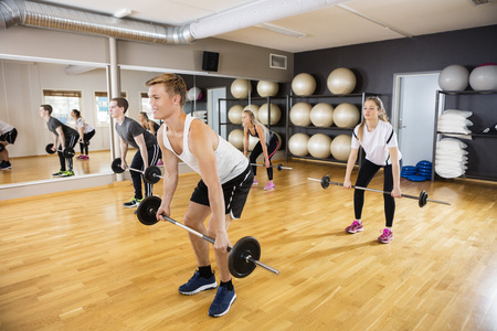 Full length of sporty young men and women lifting barbells in gym Stock Photo