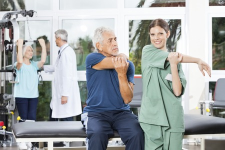 Hospital care: Portrait of nurse guiding senior man in stretching exercise at rehab fitness center