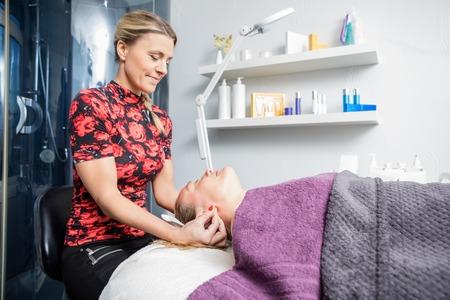 beautician: Mid adult beautician massaging female customers ear in salon Stock Photo