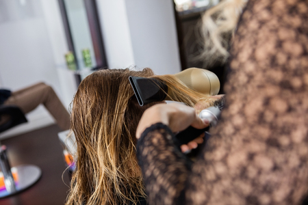 blow dryer: Cropped image of beautician styling clients hair with blow dryer and brush in salon