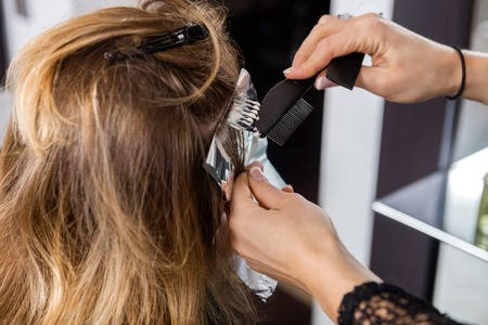 hairtician: Rear view of mature woman having her hair dyed by beautician at parlor Stock Photo