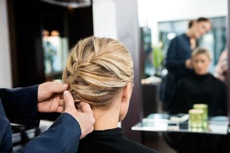 braiding: Closeup of mid adult hairdressers hands braiding clients hair at salon