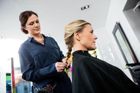mid adult female: Mid adult female hairdresser braiding clients hair in salon