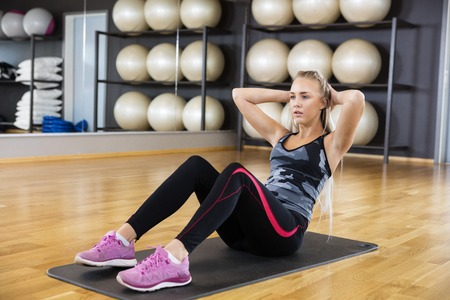 situps: Full length of determined woman performing crunches on exercise mat in gym Stock Photo