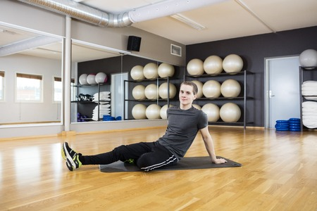 young man portrait: Full length portrait of young man resting on exercise mat in gym