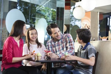 familia comiendo: Familia feliz en casuals que tienen helados mientras está sentado en la mesa en la tienda