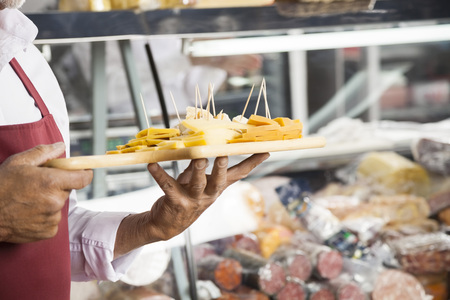 food sales: Midsection of salesman holding cutting board with assorted cheese in shop