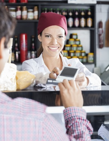 accepting: Happy saleswoman accepting payment from customer in cheese shop Stock Photo