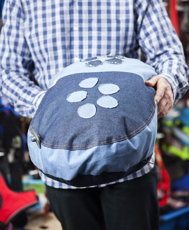 midsection: Midsection of male customer holding pet cushion in store