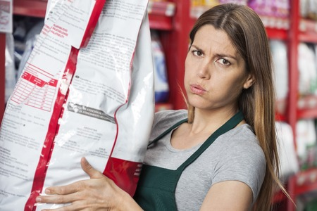 petshop: Portrait of mid adult saleswoman carrying heavy food package in pet store Stock Photo