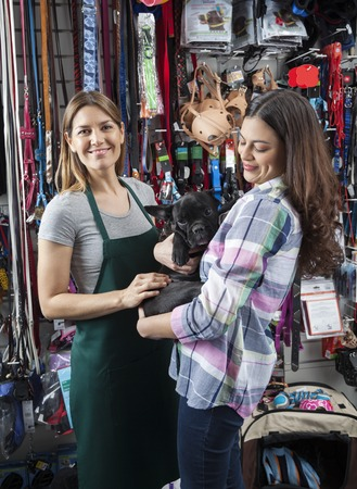 petshop: Portrait of smiling saleswoman standing with female customer carrying French Bulldog in store