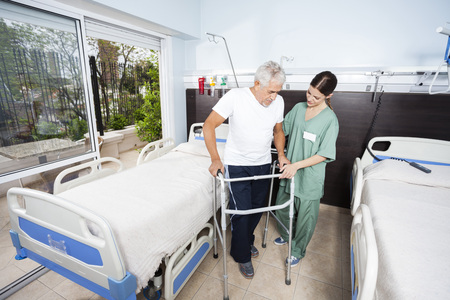 Female nurse helping senior male patient in using walker at rehab center Stockfoto