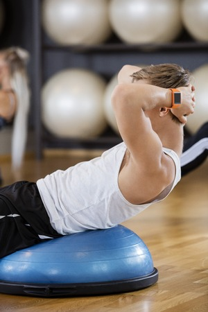 man gym: Side view of young man doing crunches in gym