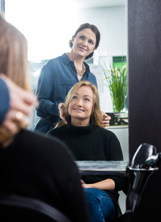 hairstylist: Reflection of mid adult female hairstylist setting clients hair in salon