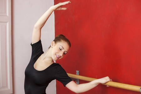 barre: Female ballet dancer stretching her hand at barre in dance studio Stock Photo