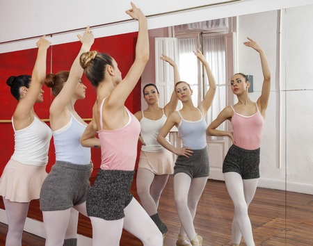 graceful: Female dancers raising arms together while performing in ballet studio Stock Photo