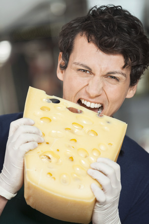 aggression: Portrait of young salesman eating cheese in store Stock Photo