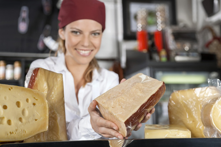 saleswoman: Portrait of young saleswoman showing cheese in grocery store