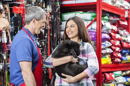 pet services: Happy woman carrying French Bulldog while standing with salesman in pet store