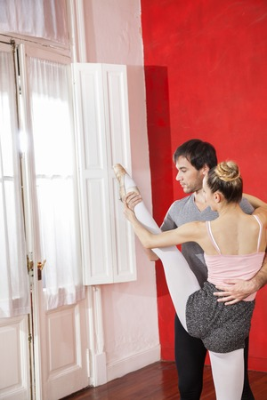 mid adult male: Mid adult male trainer helping female ballet dancer in performing split at studio