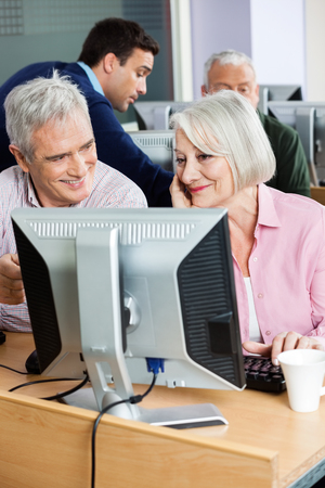 the elderly tutor: Happy senior classmates using computer at classroom while tutor explaining man in background Stock Photo