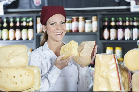 dairy product: Portrait of happy young saleswoman holding fresh cheese in store