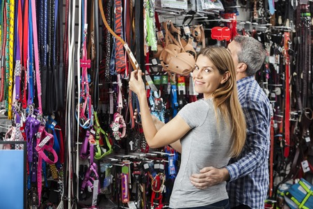 pet leash: Side view portrait of happy woman buying pet leash with man at store Stock Photo