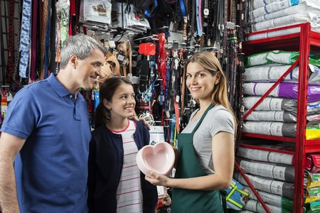 petshop: Portrait of confident saleswoman showing heart shape food bowl to father and daughter in store