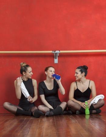 barre: Tired ballet dancers sitting on hardwood floor in training studio Stock Photo