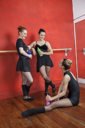 ballet bar: Full length of happy ballerinas looking at friend while holding bottles in studio