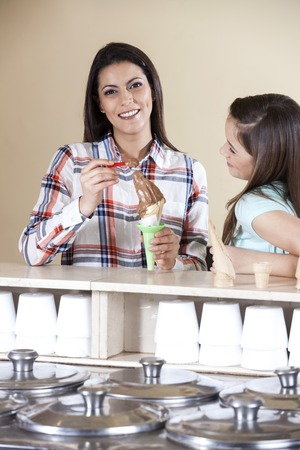 gelati: Portrait of happy woman having ice cream with daughter at counter in parlor Stock Photo