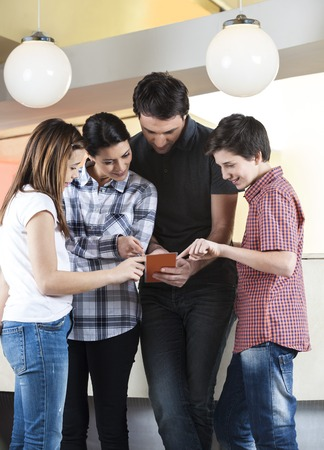 casuals: Family of four in casuals choosing ice creams from menu at counter in parlor Stock Photo